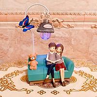 Tượng đôi tình nhân ngồi bên con gấu bông dưới ánh đèn (có con bướm)