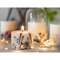 Nến thơm cao cấp bằng sáp đậu nành, với hương thơm từ tinh dầu lá quế và đinh hương, được trang trí bằng thanh quế và nụ đinh hương tự nhiên