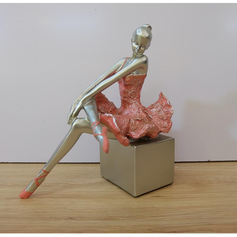 Tượng cô gái bale ngồi trên bục váy hồng
